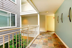 Modern apartment building hallway and door near railing. Stock Photo