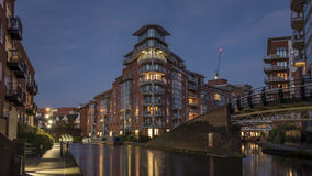 Modern apartment buildings, lit up at dusk, overlooking an urban waterway. Canal, in Birmingham, England, UK Stock Photography
