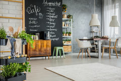 Modern apartment with chalkboard accents. Table, chairs and brick wall Royalty Free Stock Photography
