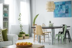 Modern apartment with communal table. Modern, white apartment with communal table, chairs, plants and sofa Stock Photography