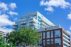 Modern apartment complex in the city tree blue sky clouds. Modern futuristic apartment complex in Toronto with trees ind the foreground and sky and clouds as royalty free stock photography