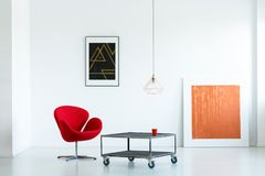 Modern apartment interior with a red armchair, movable coffee ta Royalty Free Stock Photography
