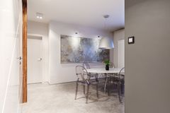 White and gray dining room. Modern apartment interior with a small, cozy dining room with white and gray walls, a round table, modern, transparent chairs, low Royalty Free Stock Images