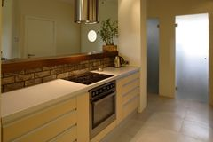Modern Apartment Kitchen. Interior view of a kitchen in a modern apartment including the stove, counters and storage drawers stock photos