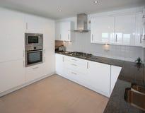 Modern Apartment Kitchen Interior. Interior of modern kitchen with black granite worktop Royalty Free Stock Photography