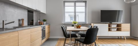 Modern wood kitchen with table. Modern apartment with open wood kitchen with table and long countertop, panorama royalty free stock photos