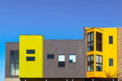 Free Modern Apartment Or Office Builing With Clean Lines And Bright Colored And Metal Siding Blocks Against Very Blue Sky Stock Images - 112291404