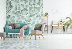 Modern apartment with turquoise couch. Open deign of modern apartment with turquoise couch in the living room and workspace against white wall Royalty Free Stock Image