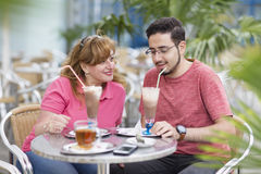 Modern arabian mother and adult son sitting together in café Royalty Free Stock Photography