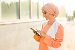 Modern Arabian muslim woman with tablet computer outdoors.  Stock Images
