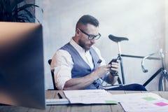 Modern arbetsplats för skäggig affärsmanMaking Great Business idé Funktionsdugligt Startup skrivbord för ung man Använd Smartphon arkivbild