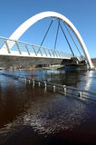 Modern arch bridge. The supporting modern arch bridge across the flooding river Royalty Free Stock Images