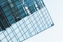 Office tower corner made of glass and steel. Modern architecture abstract fragment, office tower corner made of glass and steel under blue sky royalty free stock image
