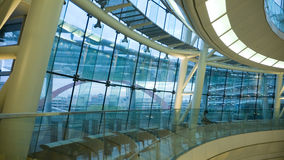Modern architecture background. Futuristic atrium environment, glass wall and metallic construction inside big public hall with sitting man Stock Photo