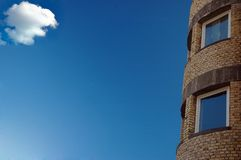 A modern architecture building. Small cloud looks after careful building of residual quarters royalty free stock photo