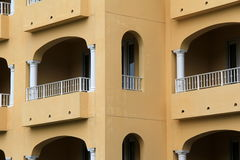 Modern architecture of building with pretty balconies. Modern architecture of hotel, with pretty balconies under arched windows royalty free stock images