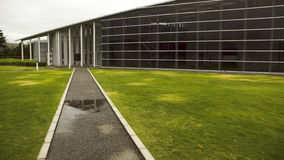 Modern architecture exterior. Modern architecture composition, glass wall and straight road to hall's entrance Stock Image