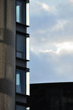 Modern architecture - facade. Modern architecture of an office building, detail of the windows with sky and clouds in the background Stock Photo