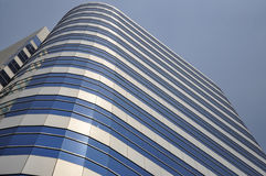 Modern glass building soaring into blue sky Royalty Free Stock Photography