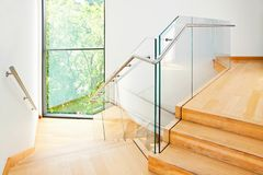 Modern architecture interior with wooden stairs. Modern architecture interior with elegant wooden stairs and glass balustrade Stock Photography