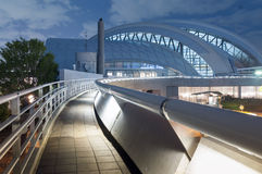 Modern architecture. Pedestrian pathway with metallic handrail leads toward modern arc dome building by night Royalty Free Stock Photography
