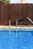 Modern arkitektur för simbassängdesign av den lyxiga ferievillan Koppla av nära exotisk simbassäng med ledstången, solstolar, sol royaltyfria bilder