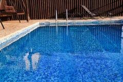 Modern arkitektur för simbassängdesign av den lyxiga ferievillan Koppla av nära exotisk simbassäng med ledstången, solstolar, sol royaltyfri fotografi