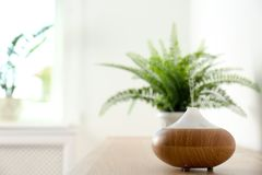 Modern aroma lamp on table. Against blurred background with space for text royalty free stock photography