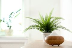 Modern aroma lamp on table. Against blurred background with space for text stock photo