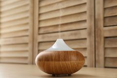 Modern aroma lamp on table. Modern aroma lamp on wooden table stock images