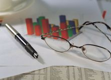Modern Article. Pen and Glasses and stock report stock photos