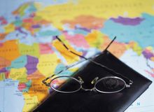 Modern Article. Passport and glasses on map royalty free stock image