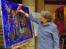 Modern artist drips paint from a plastic bottle onto his canvas. PARIS, FRANCE SEPTEMBER 4, 2015 Artist drips paint from a plastic bottle onto his colorful Stock Image