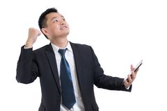 Modern asian businessman hand holding digital tablet celebrating successful. Businessman happy and smile. With Arms up while standing isolated on white stock photography