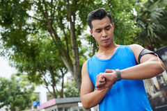 Modern Asian sportsman having training. Portrait of modern young sportsman in blue T-shirt using gadgets during training in summer park Royalty Free Stock Image
