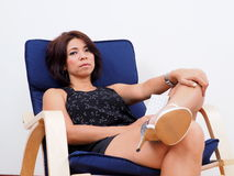 Modern Asian woman sits in a rocking chair Stock Images