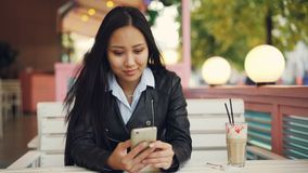 Modern Asian woman is using smartphone texting friends sitting in street cafe on windy autumn day and smiling