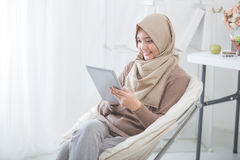 Modern asian woman using tablet pc. Modern asian woman wearing hijab using tablet pc while sitting in a living room Stock Photo