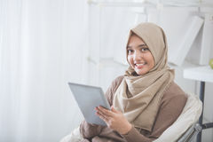 Modern asian woman using tablet pc. Modern asian woman wearing hijab using tablet pc while sitting in a living room Royalty Free Stock Photography