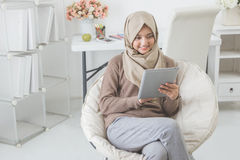 Modern asian woman using tablet pc. Modern asian woman wearing hijab using tablet pc while sitting in a living room Stock Photos
