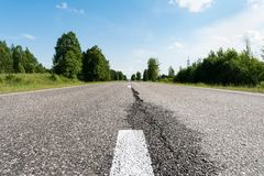 The Modern asphalt road with road marking elements. Perspective view of a two-lane highway passing through a forest. Modern asphalt road with road marking stock images