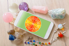 Modern astrology concept with mobile. Zodiac signs and smart phone with crystal balls. Concept of modern astrology Stock Photo