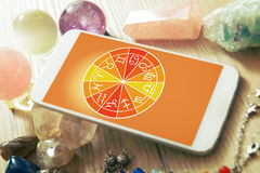 Modern astrology concept with mobile. Zodiac signs and smart phone with crystal balls. Concept of modern astrology royalty free stock photo
