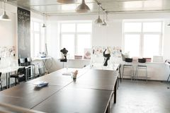 Modern  Atelier Interior in White Color. Interior of modern atelier workshop with wooden workstation in foreground and sewing dummies, no people, copy space Royalty Free Stock Photography