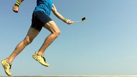 Modern Athlete Running With Smartphone on Selfie Stick. Modern athlete in gold shoes running in slow motion with his smartphone on the end of a selfie stick stock video