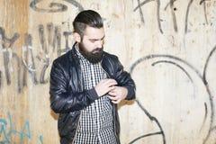 Modern and attractive man looking at his jacket. Royalty Free Stock Photos