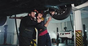 In a modern auto service center two mechanic in the uniform under the car with a flashlight fixing to the car together