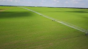 Modern automated irrigation equipment watering freshly seeded field. Irrigation of farmland to ensure the quality of the. Crop. 4k aerial view of internet stock video footage