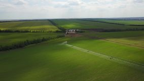 Modern automated irrigation equipment watering freshly seeded field. Irrigation of farmland to ensure the quality of the. Crop. 4k aerial view of internet stock video