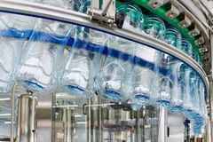 Modern automated production line for water or beverages. Closeup on empty mineral water bottles in raw materials and lines stock image